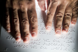 two hands reading a page of braille text
